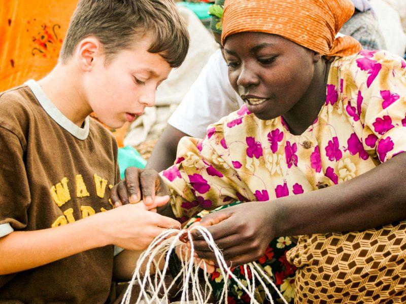 Kenyan woman show boy how to weave