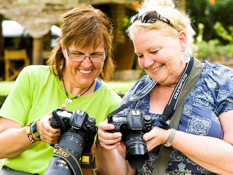 Two smiling women look at their cameras