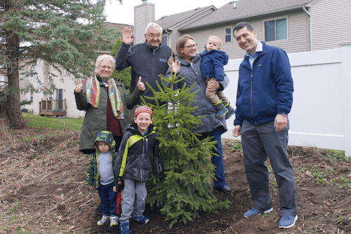 A family standing with a tree