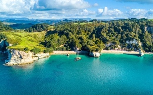 Aerial view on a remote ocean coast with small coves and mountains on the background. Coromandel, New Zealand.