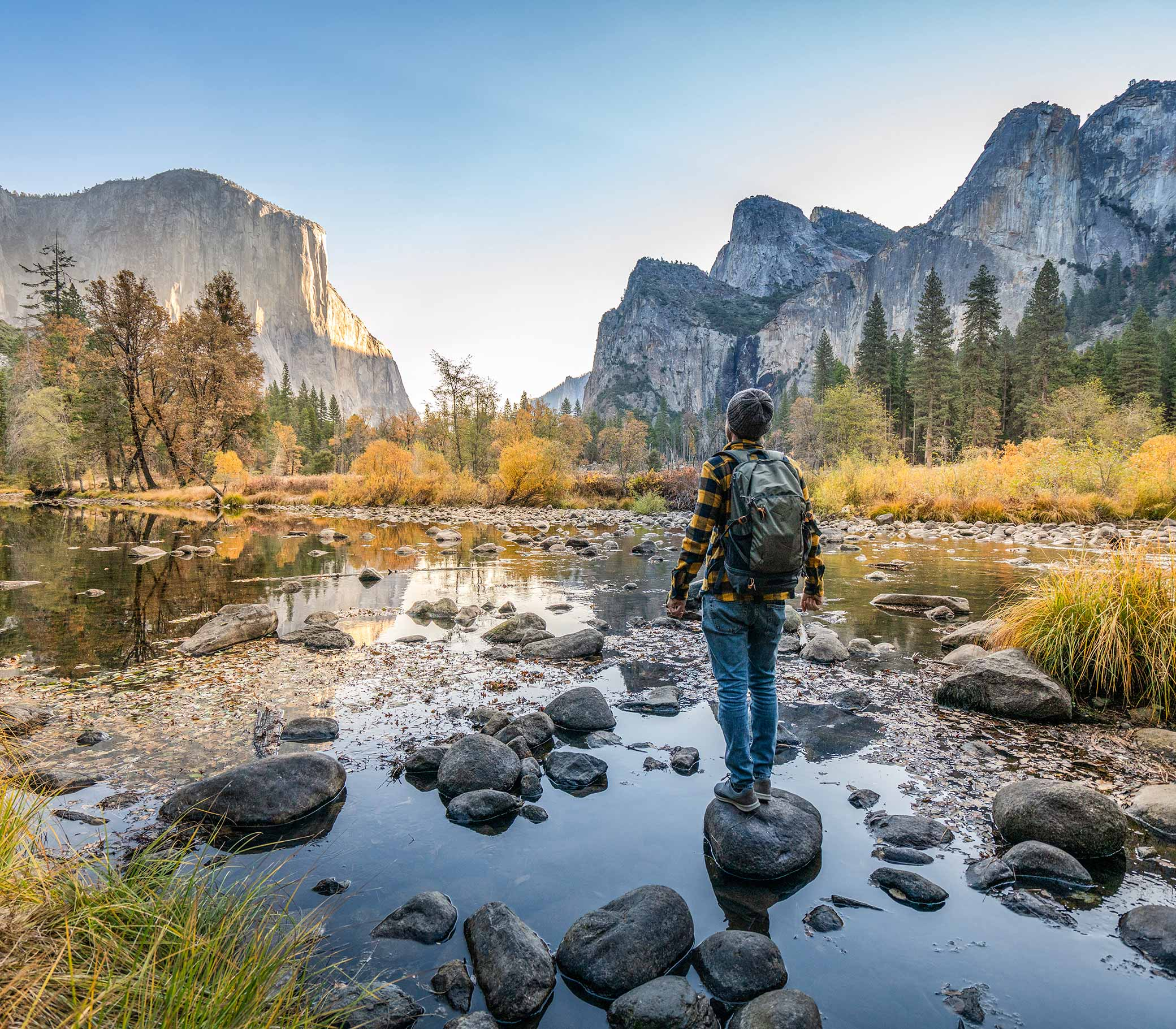 Young man contemplating Yosemite valley from the river, reflections on water surface