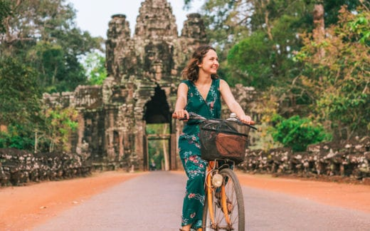 Young woman riding bicycle in Angkor Wat