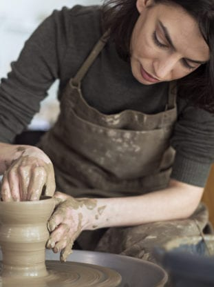 woman spinning pottery on wheel