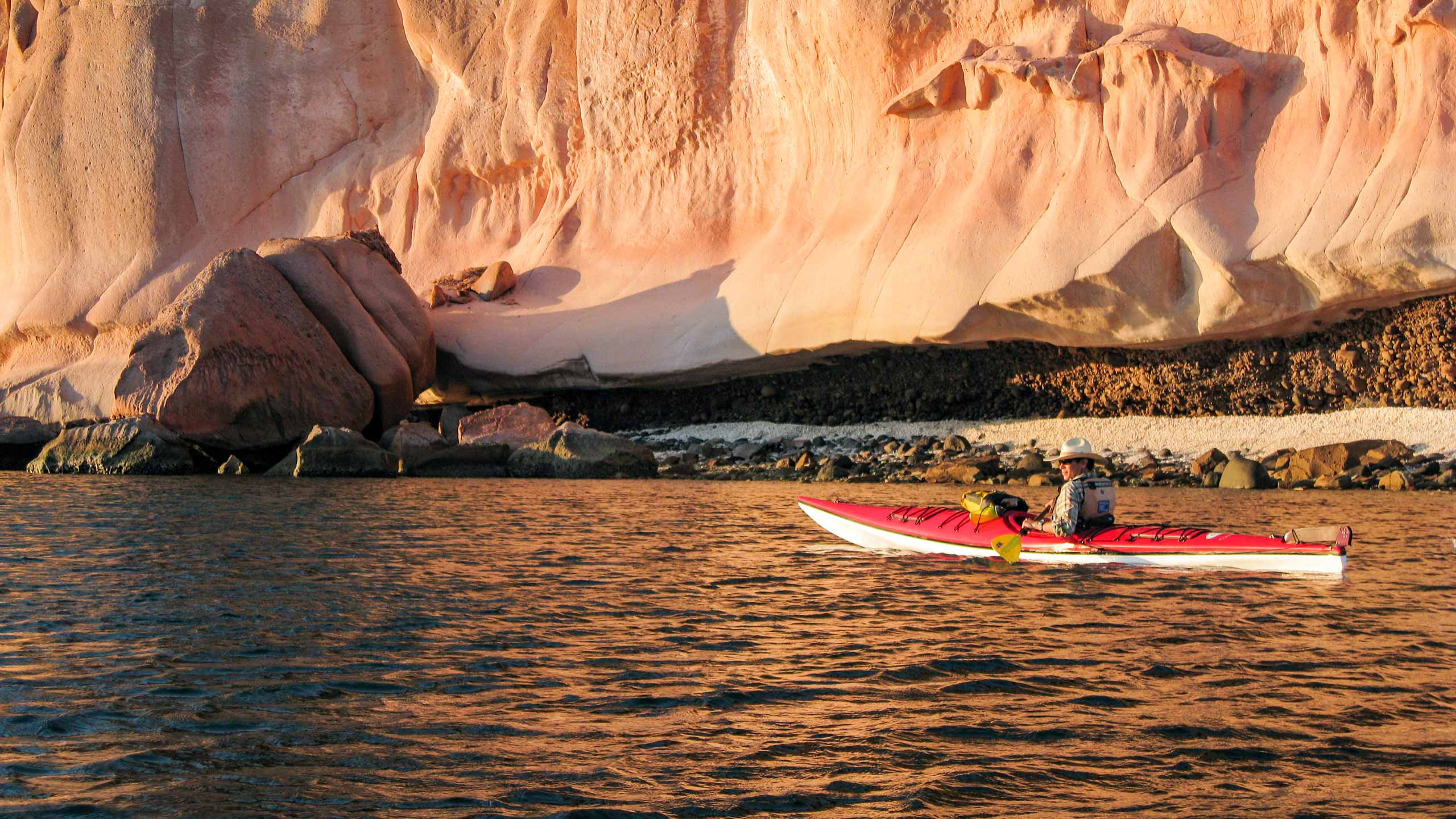 Man kayaking alone with rocky cliff beyond in Baja, Mexico