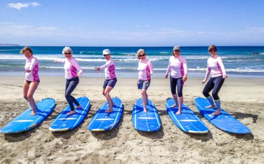 Ladies on surfboards on a beach in Baja, Mexico