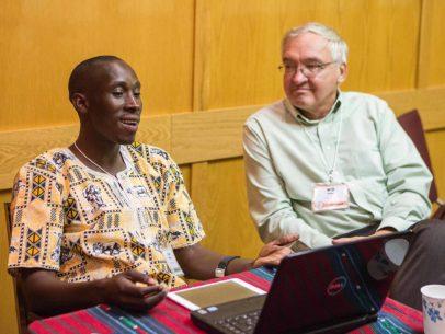 Paul Tamwenya sitting conversing with Will Weber