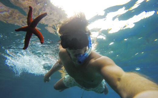 selfie of teenage boy snorkeling underwater with starfish
